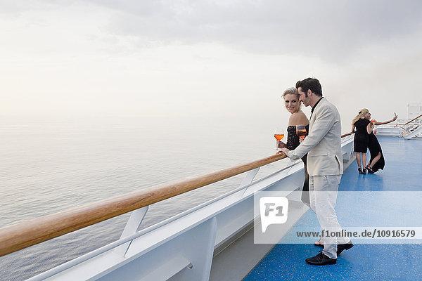 Vier Personen mit Aperitif an Deck eines Kreuzfahrtschiffes