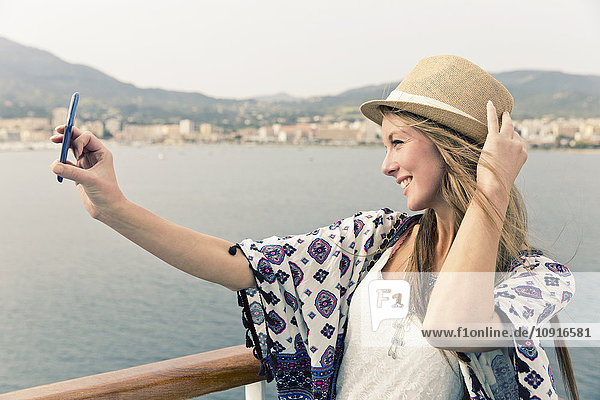Lächelnde Frau auf dem Kreuzfahrtschiff nimmt Selfie mit Smartphone