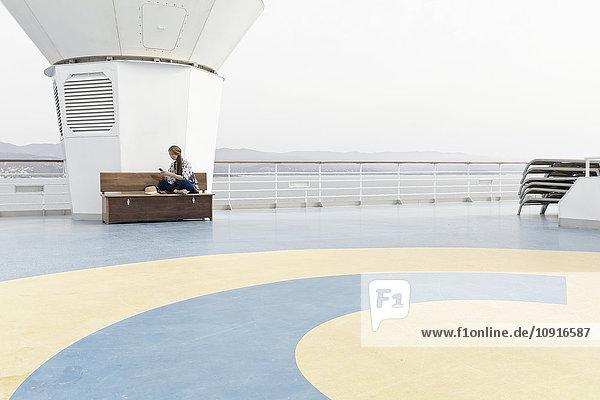 Frau sitzt auf dem Deck eines Kreuzfahrtschiffes und schaut auf ihr Smartphone.