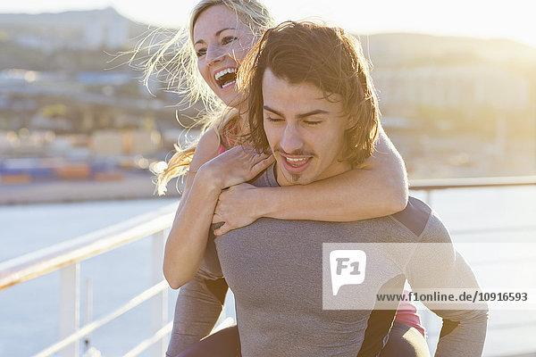 Junger Mann  der seiner Freundin eine Huckepackfahrt auf einem Kreuzfahrtschiff anbietet.