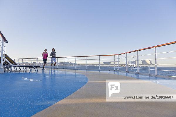 Junges Paar joggt auf dem Schiffsdeck eines Kreuzfahrtschiffes  Mittelmeer