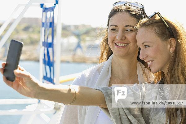 Zwei lächelnde Frauen mit einem Selfie auf einem Kreuzfahrtschiff