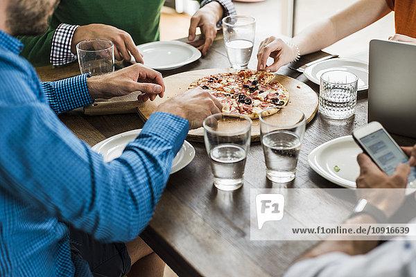 Kollegen am Tisch mit Handy und Laptop mit Pizza