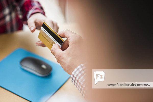 Nahaufnahme von zwei Händen mit Kreditkarte