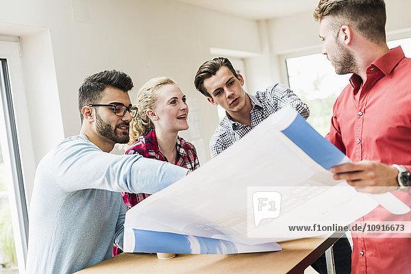 Berufseinsteiger diskutieren über den Plan im Büro