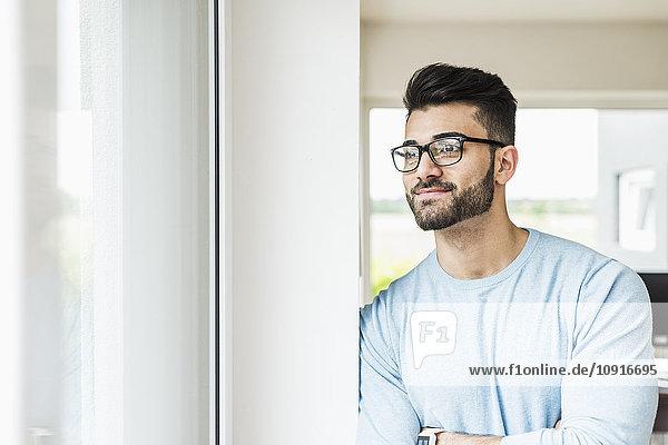Lächelnder junger Mann schaut aus dem Fenster.