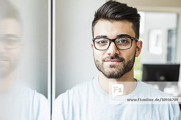 Porträt des lächelnden jungen Mannes am Fenster