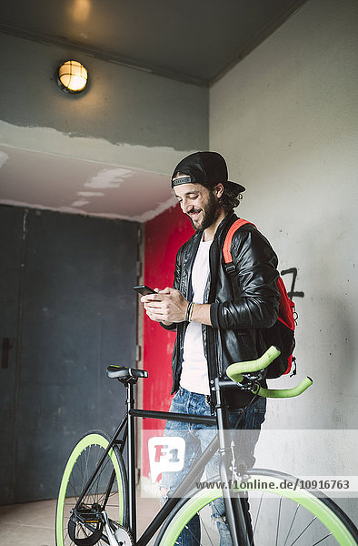 Junger Mann mit Fahrrad auf dem Smartphone