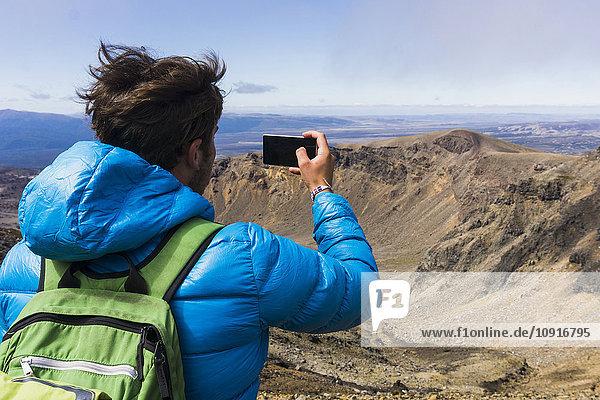 Neuseeland  Tongariro Nationalpark  Rückansicht des Wanderers beim Fotografieren mit Smartphone