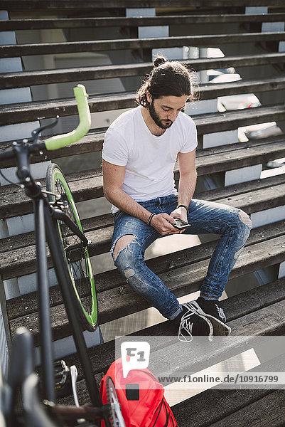 Junger Mann sitzt auf der Treppe und schaut auf das Smartphone.