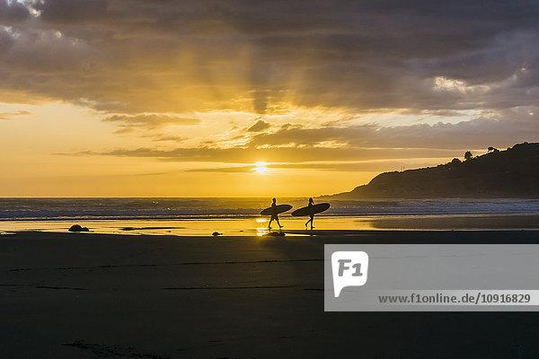 Silhouetten von zwei Personen mit Surfbrettern am Strand bei Dämmerung