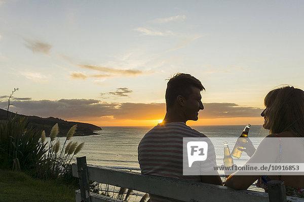 Paar sitzend auf der Bank bei Sonnenuntergang mit Getränken in Glasflaschen