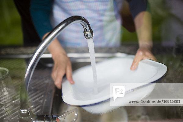 Frau beim Geschirrspülen am Spülbecken