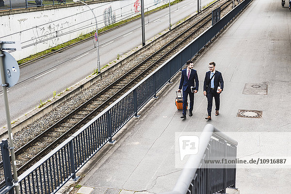 Businessmen on business trip walking with wheeled luggage