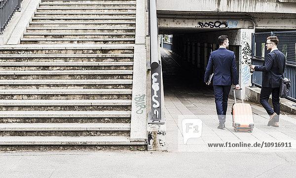 Geschäftsleute auf Geschäftsreise zu Fuß mit Rollgepäck