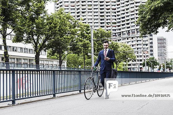 Geschäftsmann mit Fahrrad zu Fuß in der Stadt  mit Smartphone