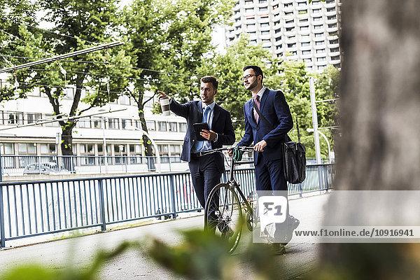 Geschäftsleute  die mit dem Fahrrad in der Stadt spazieren gehen und sich unterhalten.