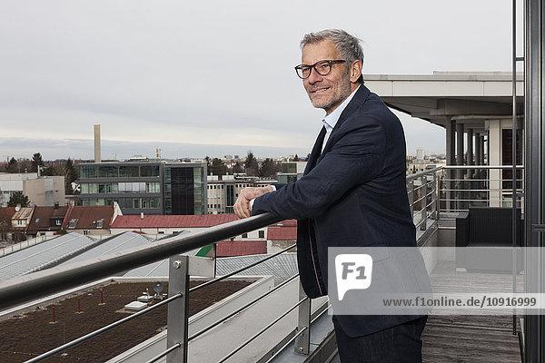 Erfolgreicher Geschäftsmann auf der Büroterrasse mit Blick über die Stadt