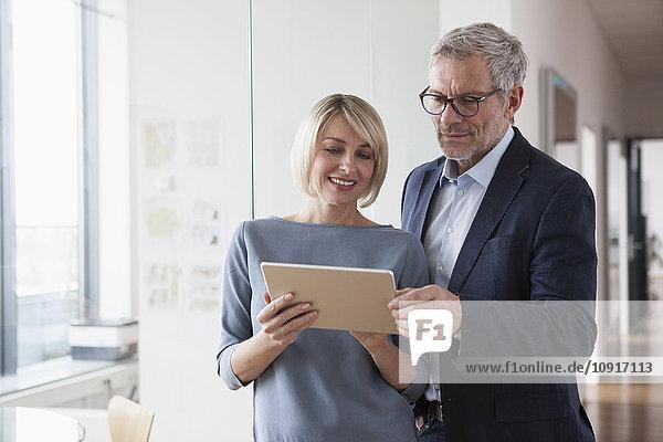 Geschäftsmann und Frau bei einer Besprechung mit Blick auf das digitale Tablett