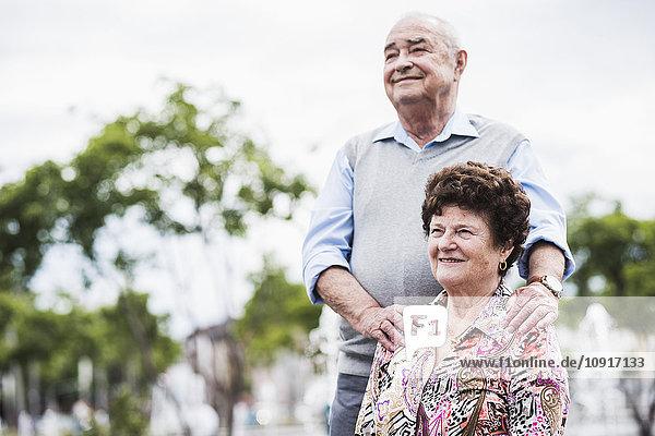 Porträt einer älteren Frau mit ihrem Mann im Hintergrund