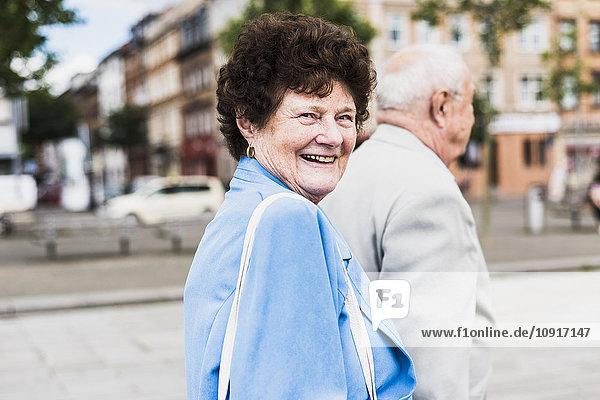 Porträt einer älteren Frau  die mit ihrem Mann spazieren geht.