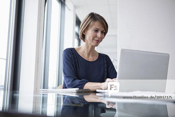 Geschäftsfrau bei der Arbeit am Laptop am Schreibtisch