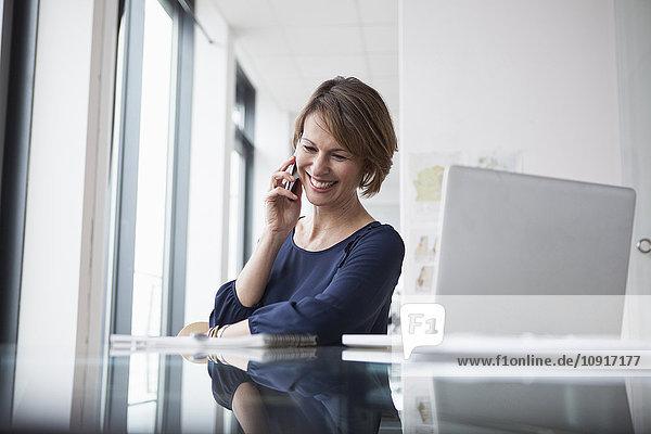 Lächelnde Geschäftsfrau am Schreibtisch am Handy