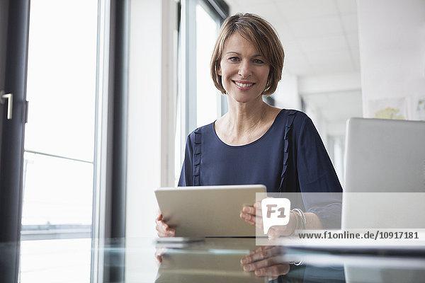 Porträt der lächelnden Geschäftsfrau mit digitalem Tablett am Schreibtisch