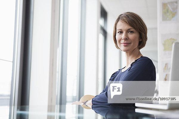 Porträt einer selbstbewussten Geschäftsfrau am Schreibtisch