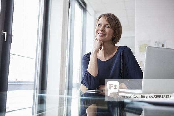 Lächelnde Geschäftsfrau am Schreibtisch
