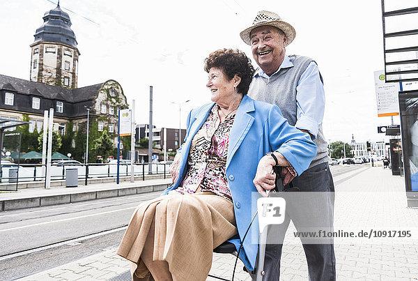 Deutschland  Mannheim  glückliches Seniorenpaar mit Rollator wartet am Bahnhof