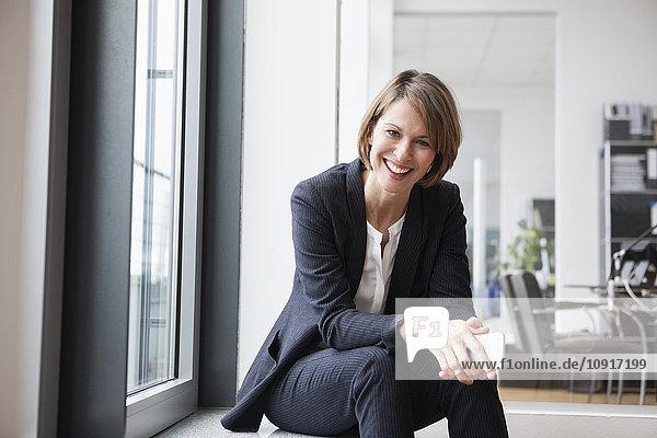 Lächelnde Geschäftsfrau am Fenster sitzend