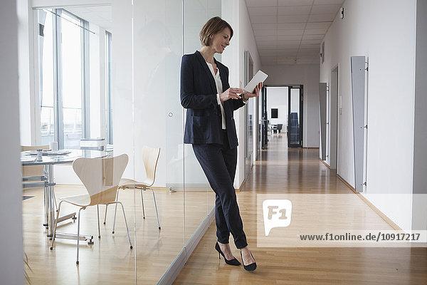 Geschäftsfrau mit digitalem Tablett in der Bürohalle