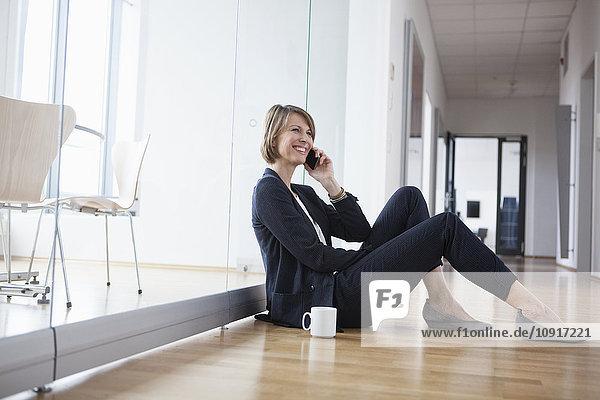 Geschäftsfrau  die sich auf der Büroetage ausruht und mit dem Handy telefoniert.