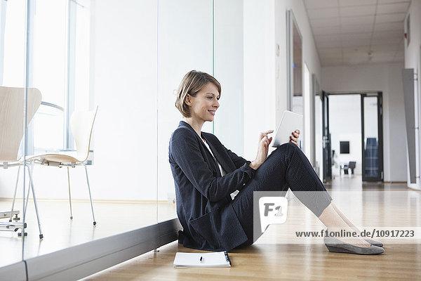 Geschäftsfrau sitzt auf der Büroetage mit digitalem Tablett