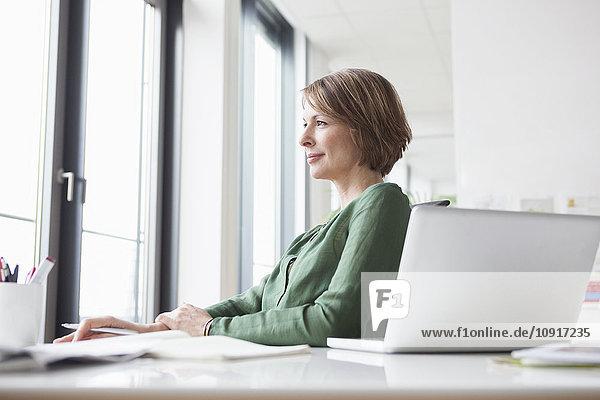 Geschäftsfrau am Schreibtisch denkend