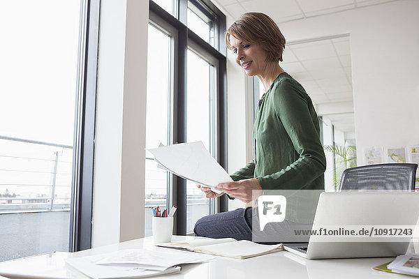 Lächelnde Geschäftsfrau beim Lesen am Schreibtisch