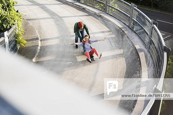Junges Paar mit Skateboard im Parkhaus