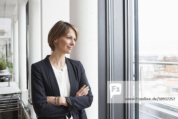 Geschäftsfrau mit Blick aus dem Fenster