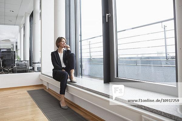 Lächelnde Geschäftsfrau auf der Fensterbank sitzend