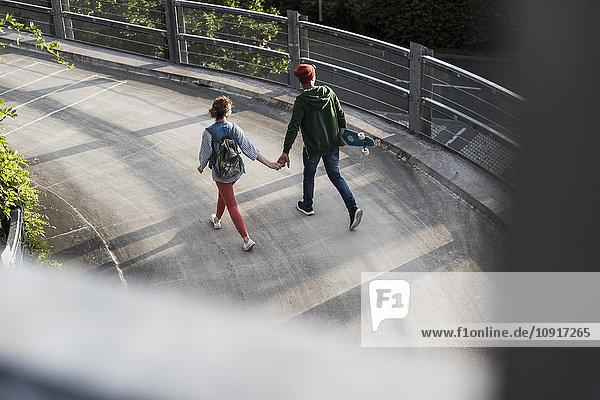 Junges Paar mit Skateboard läuft Hand in Hand im Parkhaus