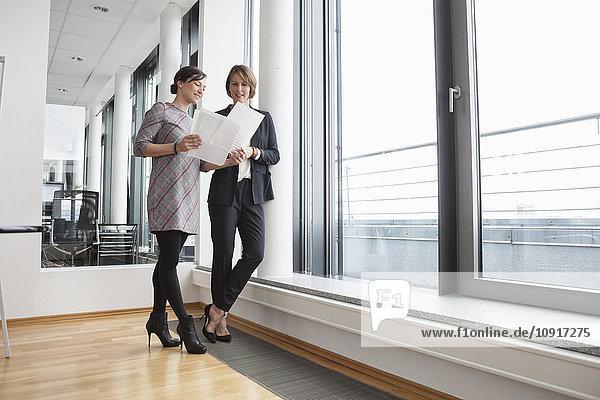 Zwei Geschäftsfrauen diskutieren Dokumente am Fenster