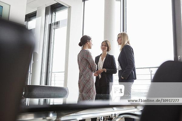 Drei Geschäftsfrauen diskutieren am Fenster
