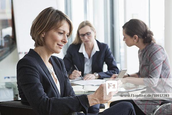Geschäftsfrau mit Handy in einer Besprechung