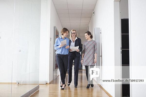 Drei Geschäftsfrauen laufen und reden in der Bürohalle