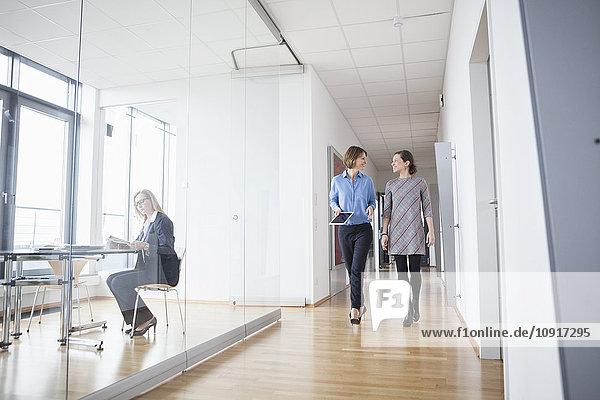 Zwei Geschäftsfrauen gehen und reden in der Bürohalle