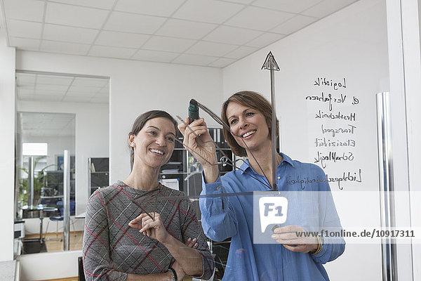 Geschäftsfrau mit Kollegin Zeichnung auf Glasscheibe im Büro