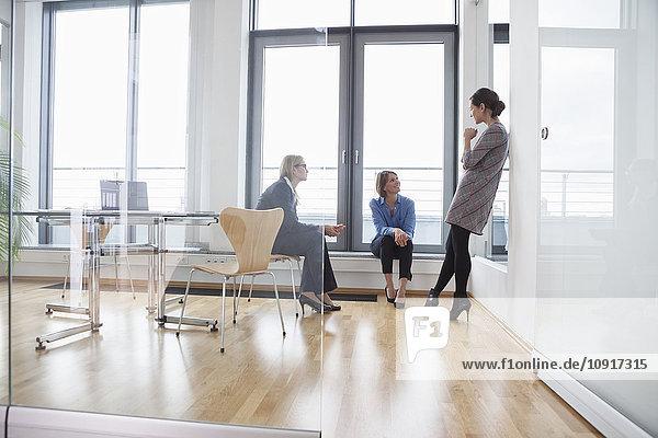 Drei Geschäftsfrauen im Gespräch am Fenster