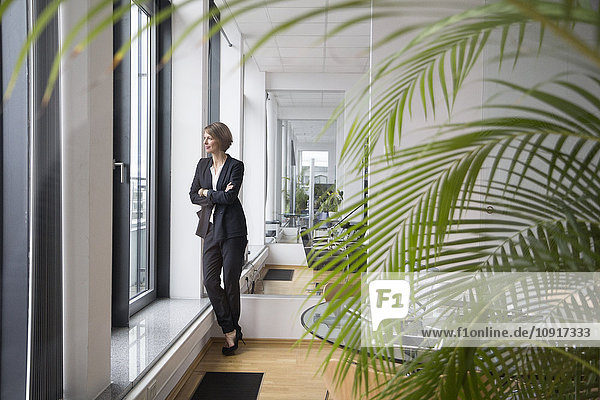Geschäftsfrau im Büro mit Blick aus dem Fenster