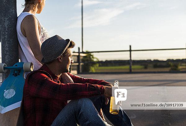 Junges Paar mit Skateboard und Bierflasche beim Sonnenuntergang